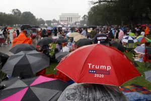 Robert Campbell, bottom right, of Charleston, W.Va., tries to stay dry under an umbrella hat as rain falls before Independence Day celebrations, Thursday, July 4, 2019, on the National Mall in Washington. (AP Photo/Patrick Semansky)